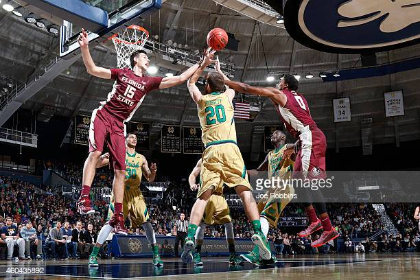Austin Burgett of the Notre Dame Fighting Irish fights for a rebound against Boris Bojanovsky and Phil Cofer of the Florida State Seminoles during...