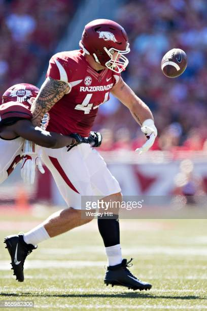 Austin Cantrell of the Arkansas Razorbacks fumbles the ball after being hit by Terrill Hanks of the New Mexico State Aggies at Donald W Reynolds...