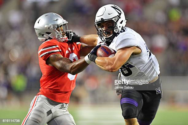 Austin Carr of the Northwestern Wildcats fends off Damon Arnette of the Ohio State Buckeyes while picking up 27yards in the fourth quarter at Ohio...