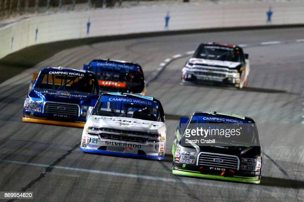 Austin Cindric driver of the Fitzgerald Glider Kits Ford and Johnny Sauter driver of the ISMConnect Chevrolet lead a pack of cars during the NASCAR...