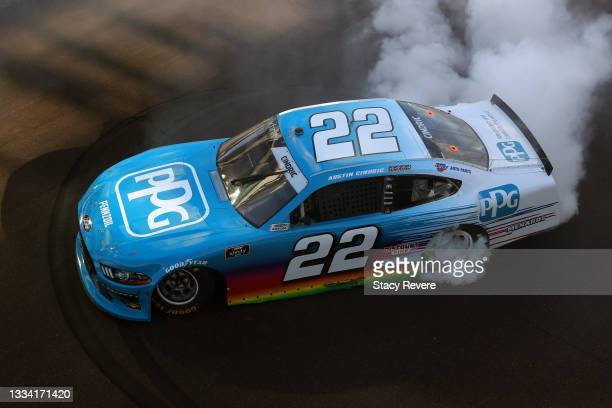 Austin Cindric, driver of the PPG Ford, celebrates with a burnout after winning the NASCAR Xfinity Series Pennzoil 150 at the Brickyard at...