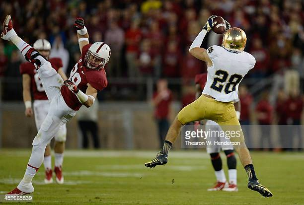 Austin Collinsworth of the Notre Dame Fighting Irish intercepts this pass over the head of Devon Cajuste of the Stanford Cardinal during the second...