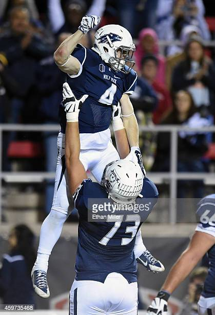 Austin Corbett of the Nevada Wolf Pack lifts teammate Kendall Brock in the air after he scored a touchdown against the UNLV Rebels during their game...