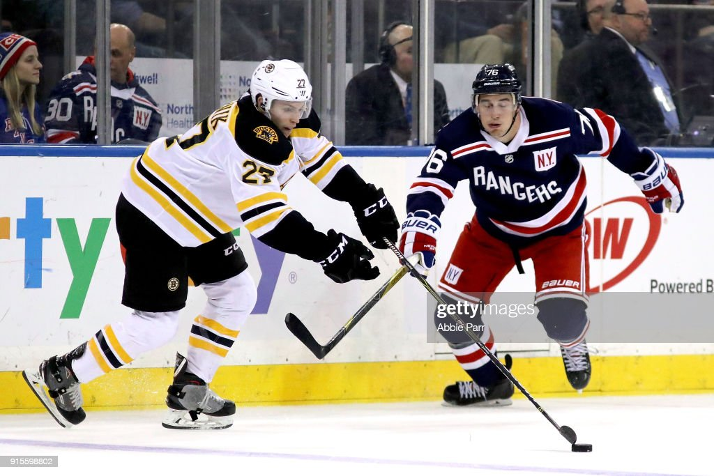 Austin Czarnik #27 of the Boston Bruins fights for the puck against Brady Skjei #76 of the New York Rangers in the third period during their game at Madison Square Garden on February 7, 2018 in New York City.