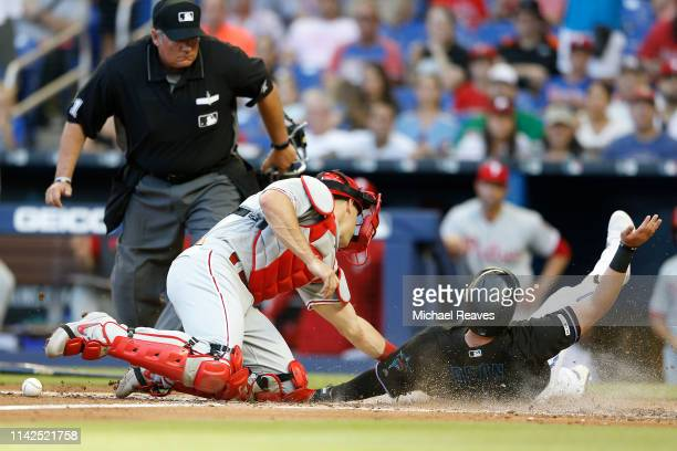 Austin Dean of the Miami Marlins slides safely home past the tag of JT Realmuto of the Philadelphia Phillies during the second inning at Marlins Park...
