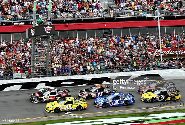 Austin Dillon driver of the DOW Chevrolet and Matt Kenseth driver of the Dollar General Toyota lead the field past the green flag to start the NASCAR...