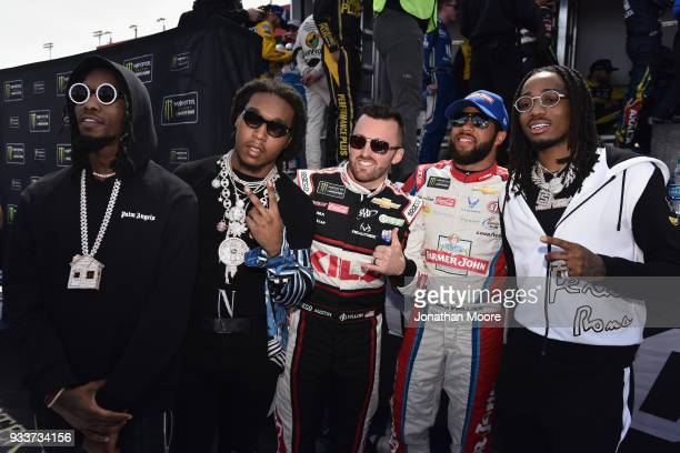 Austin Dillon driver of the Dow Coating Chevrolet and Darrell Wallace Jr driver of the Farmer John Chevrolet pose for a photo with Migos prior to the...