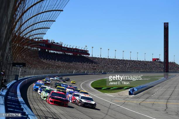 Austin Dillon driver of the Dow Coatings Chevrolet and Kevin Harvick driver of the Jimmy John's Ford lead the field to turn one after taking the...