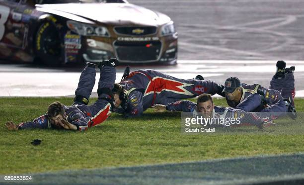 Austin Dillon driver of the DOW Salutes Veterans Chevrolet and his crew slide in the infield grass in celebration of winning the Monster Energy...