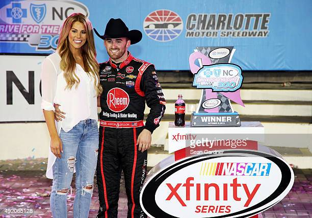 Austin Dillon driver of the Rheem Chevrolet celebrates in victory lane with his girlfriend and Titans cheerleader Whitney Ward after winning the...