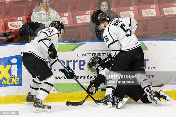 Austin Eastman and teammate Elie Berube of the Gatineau Olympiques battle for the puck with Philippe Sanche of the BlainvilleBoisbriand Armada...