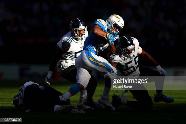 Austin Ekeler of Los Angeles Chargers is brought down by Jayon Brown of Tennessee Titans during the NFL International Series match between Tennessee...