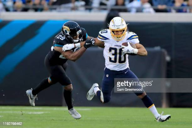 Austin Ekeler of the Los Angeles Chargers attempts to run past Marcus Gilchrist of the Jacksonville Jaguars during the game at TIAA Bank Field on...