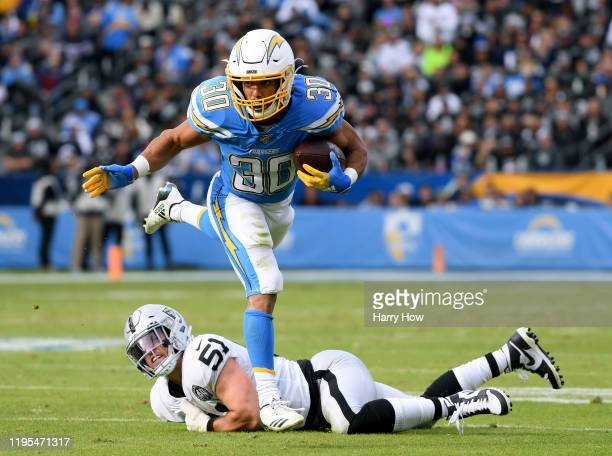 Austin Ekeler of the Los Angeles Chargers breaks a tackle from Will Compton of the Oakland Raiders during the second quarter at Dignity Health Sports...