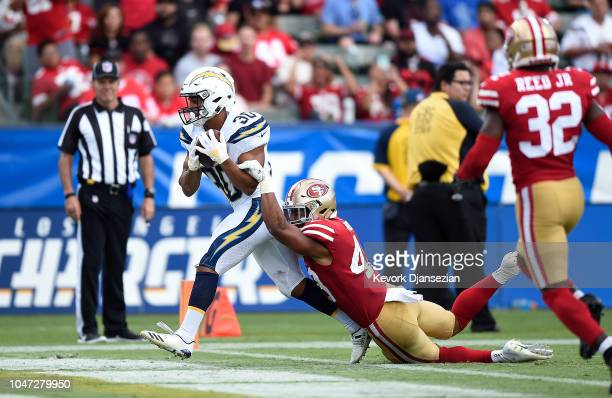Austin Ekeler of the Los Angeles Chargers catches a pass and run into the end zone for a touchdown against Fred Warner of the San Francisco 49ers...