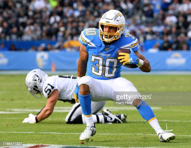 Austin Ekeler of the Los Angeles Chargers cuts back after breaking a tackle from Will Compton of the Oakland Raiders during the second quarter at...