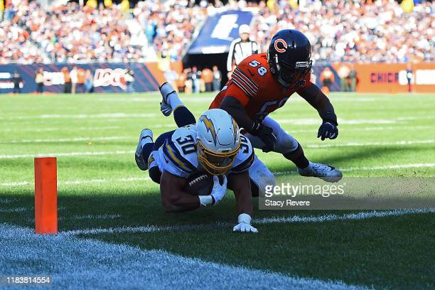 Austin Ekeler of the Los Angeles Chargers dives for a touchdown in front of Roquan Smith of the Chicago Bears during the second half of a game at...