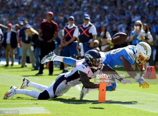 Austin Ekeler of the Los Angeles Chargers fumbles the football as he is hit by Kareem Jackson of the Denver Broncos during the last play of the...