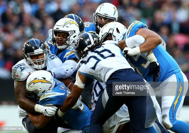 Austin Ekeler of the Los Angeles Chargers is tackled by Austin Johnson of the Tennessee Titans during the NFL International Series game between...
