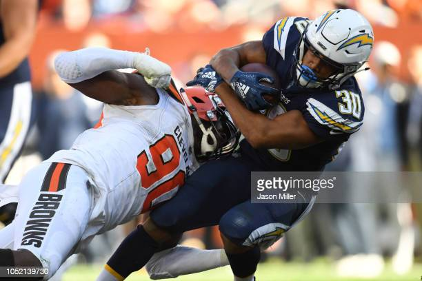 Austin Ekeler of the Los Angeles Chargers is tackled by Emmanuel Ogbah of the Cleveland Browns in the second half at FirstEnergy Stadium on October...