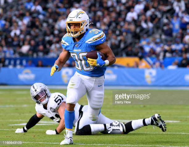 Austin Ekeler of the Los Angeles Chargers runs after breaking a tackle from Will Compton of the Oakland Raiders during the second quarter at Dignity...