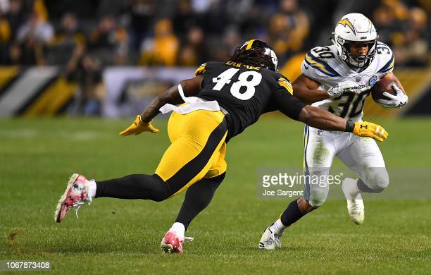 Austin Ekeler of the Los Angeles Chargers rushes the ball against Bud Dupree of the Pittsburgh Steelers in the second half during the game at Heinz...
