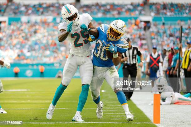 Austin Ekeler of the Los Angeles Chargers scores a touchdown past Xavien Howard of the Miami Dolphins during the second quarter at Hard Rock Stadium...