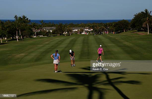 Austin Enst Paige Mackenzie and Brittany Lincicome putt on the 14th green during the first round of the LPGA LOTTE Championship Presented by J Golf...