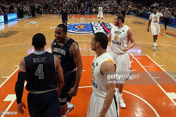 Austin Freeman of the Georgetown Hoyas celebrates after a play with teammate Chris Wright as Joe Mazzulla and Cam Thoroughman of the West Virginia...