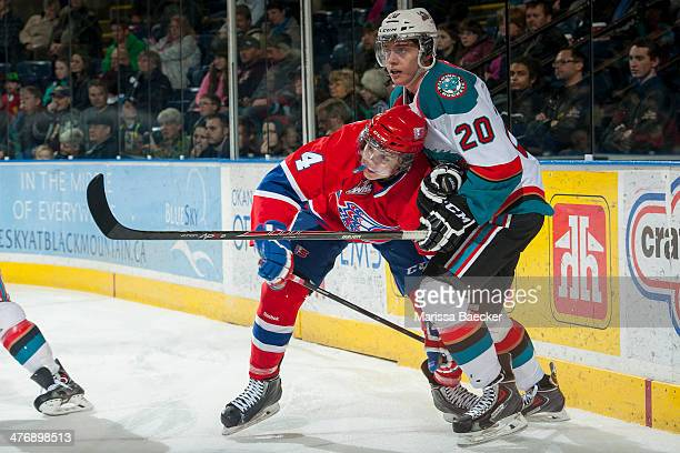 Austin Glover of the Kelowna Rockets checks Jeremy McIntosh of the Spokane Chiefs during the first period on March 5, 2014 at Prospera Place in...