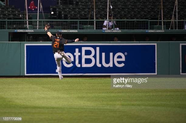 Austin Hays of the Baltimore Orioles is unable to corral a ground rule double in the sixth inning against the Boston Red Sox on Opening Day at Fenway...