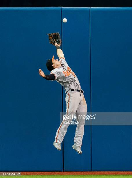 Austin Hays of the Baltimore Orioles jumps for a ball against the the wall against the Toronto Blue Jays in the seventh inning during their MLB game...