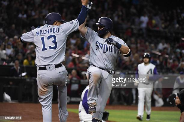 Austin Hedges of the San Diego Padres celebrates with teammate Manny Machado after hitting a three run home run off of Zack Godley of the Arizona...