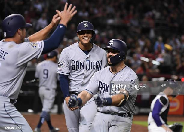 Austin Hedges of the San Diego Padres celebrates with teammate Manny Machado and Hunter Renfroe after hitting a three run home run off of Zack Godley...