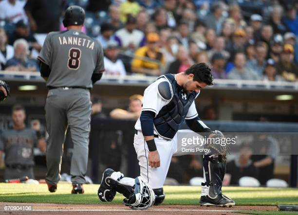 Austin Hedges of the San Diego Padres goes down on one knee after a collision a the plate during the second inning of a baseball game against the...