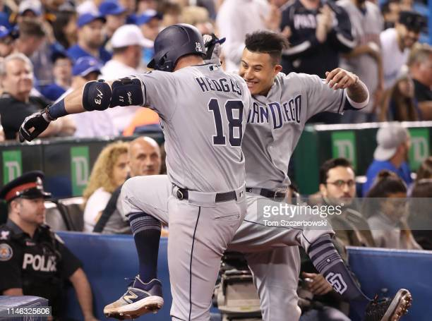 Austin Hedges of the San Diego Padres is congratulated by Manny Machado after hitting a grand slam home run in the fourth inning during MLB game...