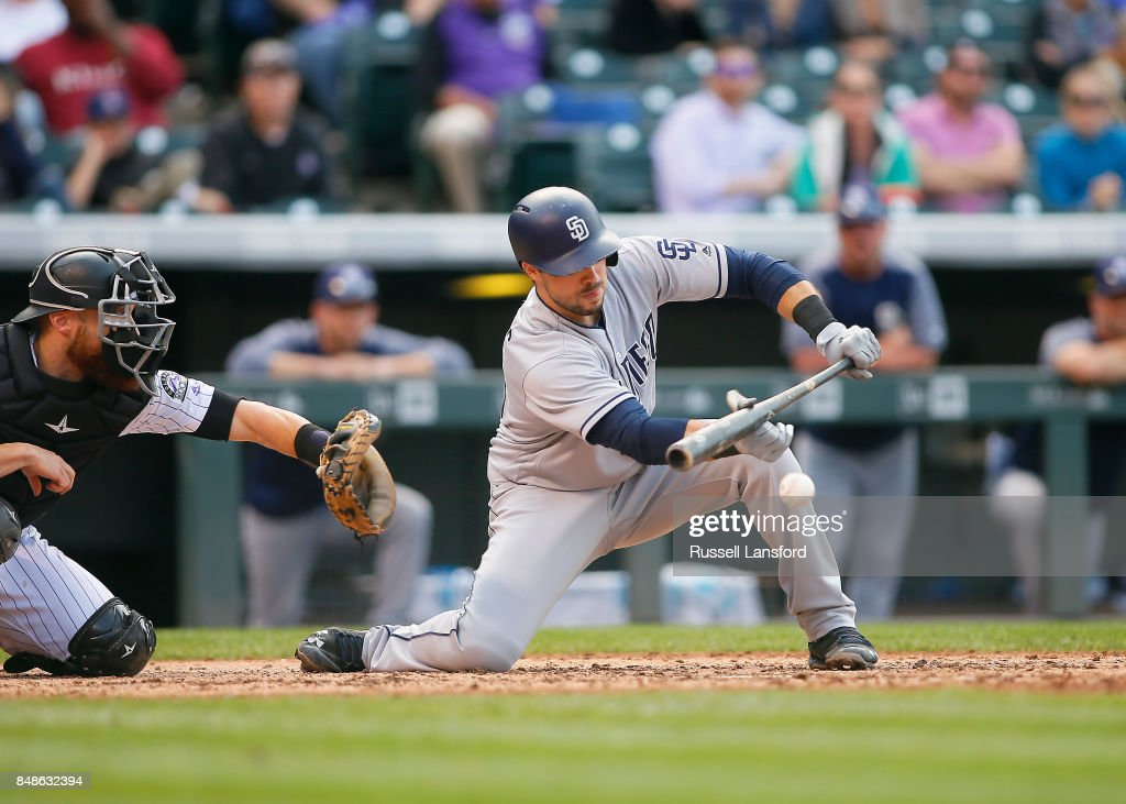 Austin Hedges #18 of the San Diego Padres lays down a sacrifice bunt for the go-ahead run in the ninth inning of a regular season MLB game between the Colorado Rockies and the visiting San Diego Padres at Coors Field on September 17, 2017 in Denver, Colorado.