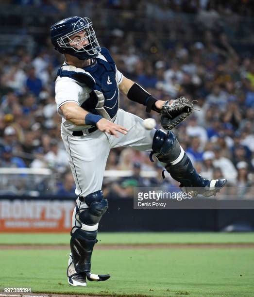 Austin Hedges of the San Diego Padres throws to first base on a ball hit by Cody Bellinger of the Los Angeles Dodgers during the fourth inning of a...