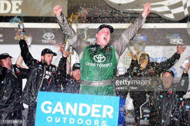 Austin Hill driver of the CHIBA Toyopet Toyota celebrates in victory lane after winning the NASCAR Gander Outdoors Truck Series NextEra Energy 250 at...