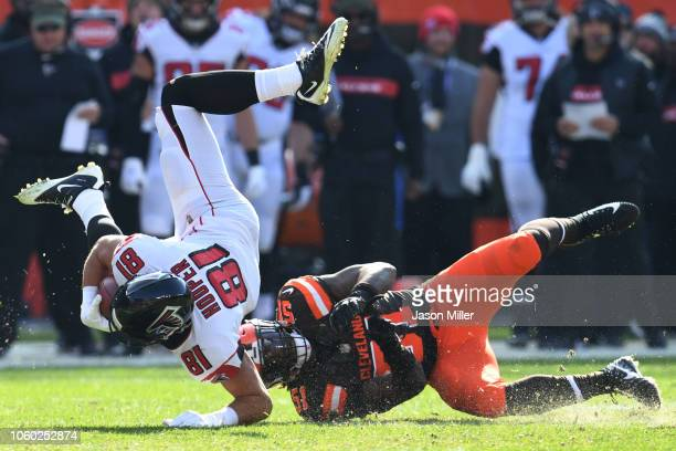 Austin Hooper of the Atlanta Falcons flies through the air after being tackled by Jamie Collins of the Cleveland Browns in the first half at...