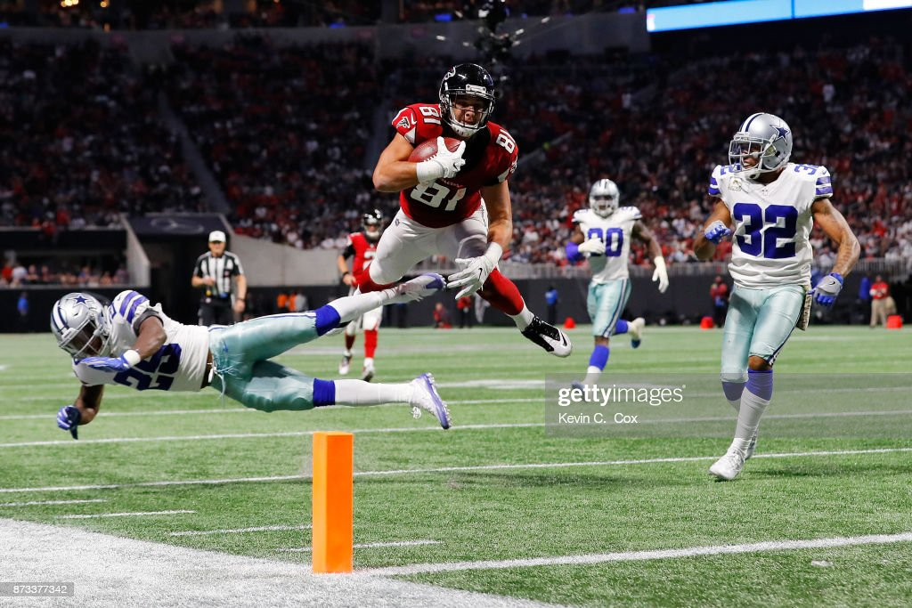 Austin Hooper #81 of the Atlanta Falcons leaps over Xavier Woods #25 of the Dallas Cowboys in an attempt to score a touchdown during the second half at Mercedes-Benz Stadium on November 12, 2017 in Atlanta, Georgia.
