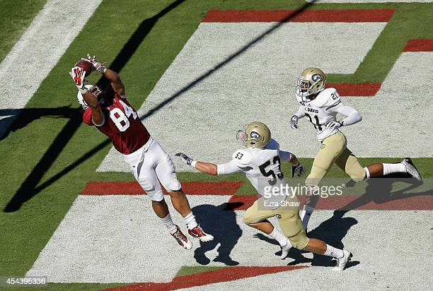 Austin Hooper of the Stanford Cardinal catches a touchdown pass in front of Russell Reeder and Darryl Graham of the UC Davis Aggies at Stanford...