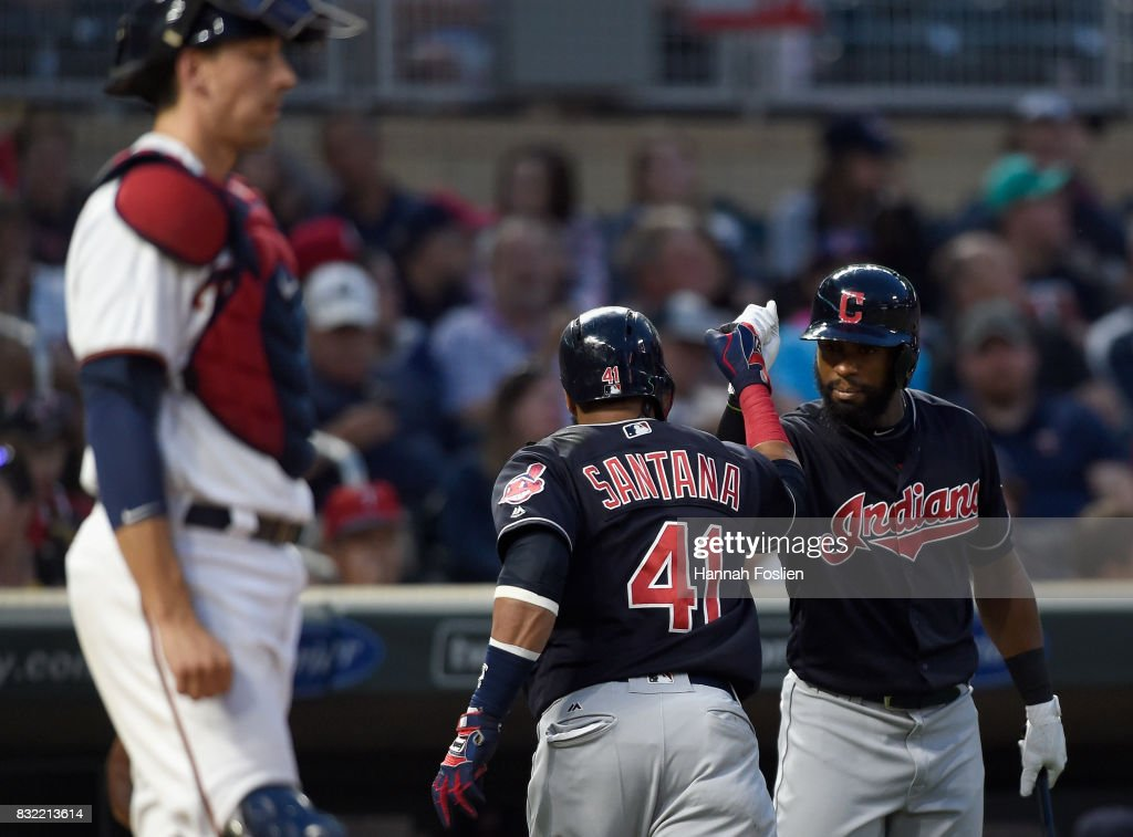 Austin Jackson #26 of the Cleveland Indians congratulates teammate Carlos Santana #41 on a solo home run as Jason Castro #21 of the Minnesota Twins looks on during the fourth inning of the game on August 15, 2017 at Target Field in Minneapolis, Minnesota. The Indians defeated the Twins 8-1.