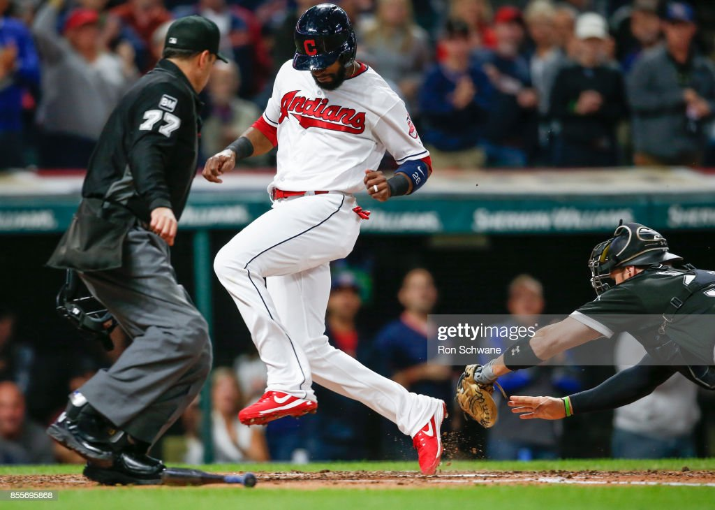 Austin Jackson #26 of the Cleveland Indians scores past Kevan Smith #36 of the Chicago White Sox on a double by Jose Ramirez #11 as home plate umpire Jim Reynolds #77 looks on during the second inning at Progressive Field on September 29, 2017 in Cleveland, Ohio.