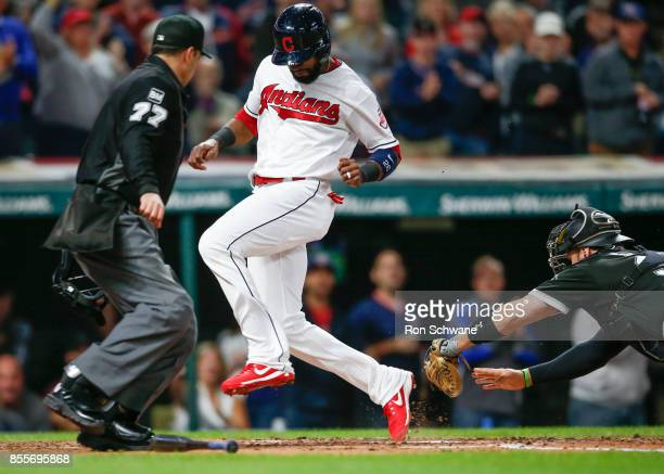 Austin Jackson of the Cleveland Indians scores past Kevan Smith of the Chicago White Sox on a double by Jose Ramirez as home plate umpire Jim...