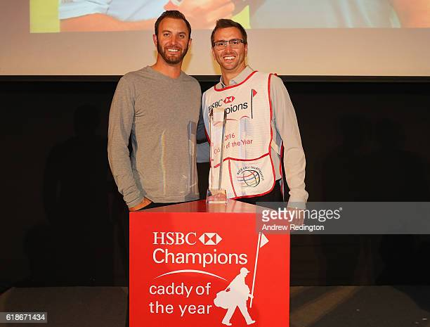 Austin Johnson poses next to his player/brother Dustin Johnson of the United States after winning the Caddy of the Year Award following the first...