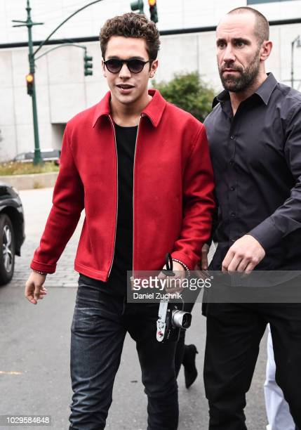 Austin Mahone is seen wearing a red jacket black shirt black jeans and shoes with a Leica camera outside the Brandon Maxwell show during New York...
