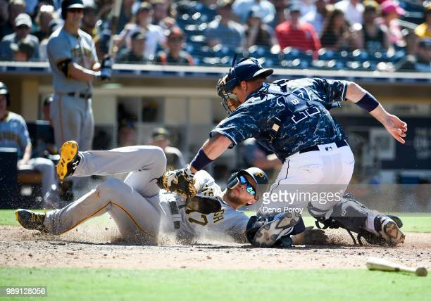 Austin Meadows of the Pittsburgh Pirates is tagged out at the plate by AJ Ellis of the San Diego Padres during the seventh inning a baseball game at...