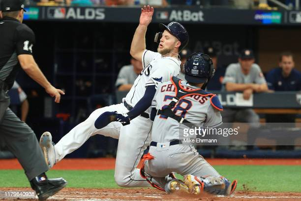 Austin Meadows of the Tampa Bay Rays slides safely past the tag of Robinson Chirinos of the Houston Astros to score a run during the fourth inningin...