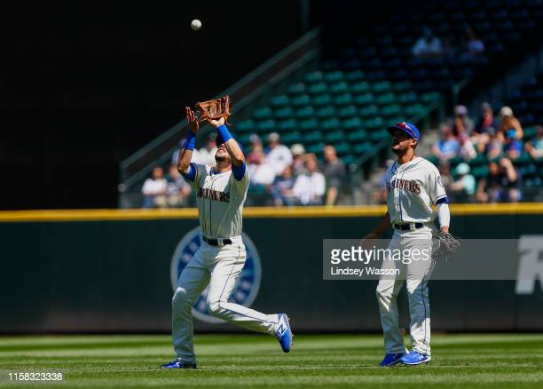 Austin Nola of the Seattle Mariners catches a pop fly hit by Miguel Cabrera of the Detroit Tigers as Kristopher Negron looks on in the first inning...